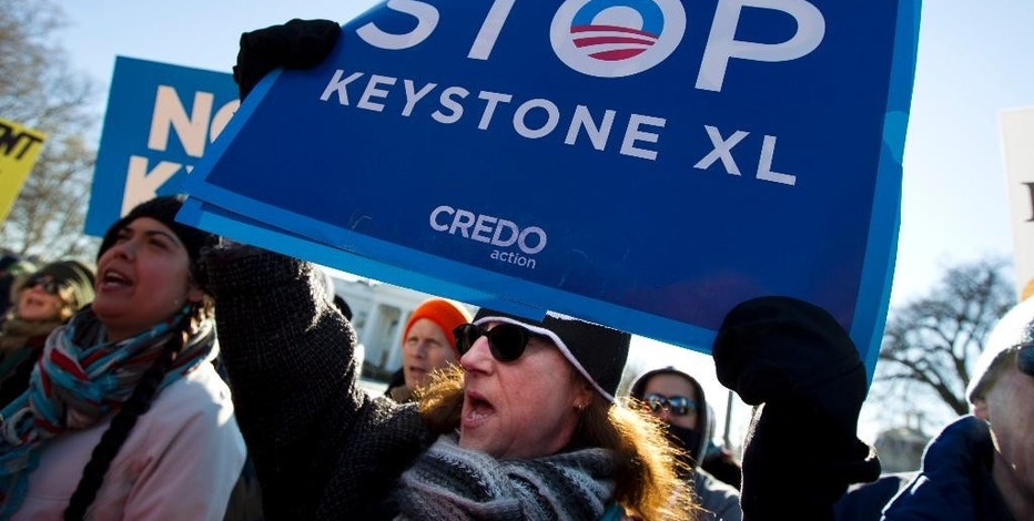 Demonstrator Sharon Garlena and others rally in support of Obama's pledge to veto any legislation approving the Keystone XL pipeline, outside the White House in Washington on Saturday, Jan. 10, 2015.  (AP Photo/Jose Luis Magana)
