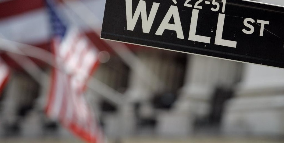 FILE - This May 11, 2007 file photo shows a Wall Street sign in front of the flag-draped facade of the New York Stock Exchange.  U.S. stocks are edging higher on Thursday, April 23, 2015,  as traders pore over more earnings news.  (AP Photo/Richard Drew, File)