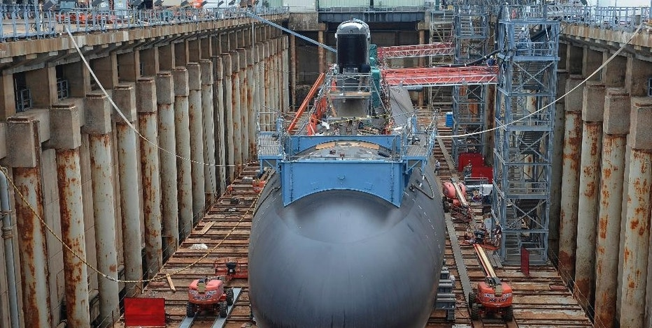 In this Thursday, July 30, 2015 photo, shipyard workers at General Dynamics Electric Boat prepare the submarine Illinois for float-off in Groton, Conn.  The U.S. Navy is using a new painting process and dozens of other innovations aimed at reducing the maintenance needs for attack submarines, which are coming out of service faster than they can be replaced. (AP Photo/Jessica Hill)