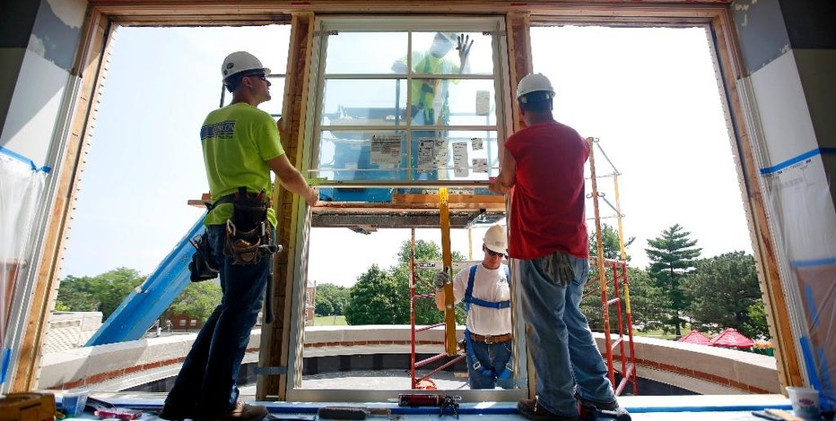 In this Wednesday, July 15, 2015 photo, Chris Esch, left, and Tony Ede, both of Conlon Construction Co., install a new window as Bryant Elementary School undergoes renovations, in Dubuque, Iowa. The Commerce Department reports on U.S. construction spending in June on Monday, Aug. 3, 2015. (Mike Burley/Telegraph Herald via AP) MANDATORY CREDIT