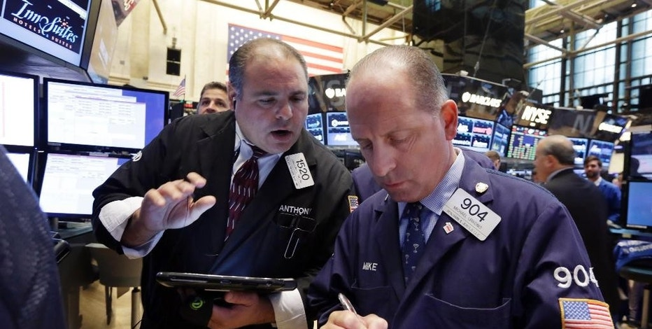 Traders Anthony Riccio, left, and Michael Urkonis work on the floor of the New York Stock Exchange, Monday, Aug. 3, 2015. Stocks are opening slightly lower in the U.S. as energy companies slide along with the price of crude oil. (AP Photo/Richard Drew)