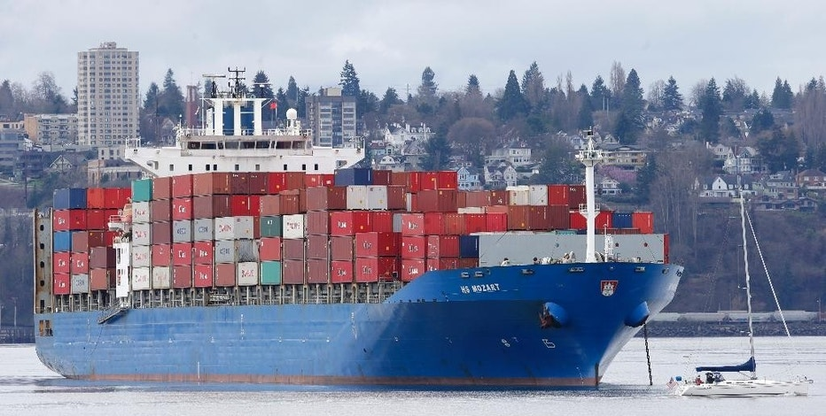 FILE - In this Feb. 20, 2015 file photo, a sailboat moves past the 925-foot long HS Mozart cargo ship, operated by the German shipping company Hansa Shipping, anchored in Commencement Bay near the Port of Tacoma, Wash. The Commerce Department reports on the U.S. trade gap for June 2015 on Wednesday, Aug. 5, 2015. (AP Photo/Ted S. Warren, File)