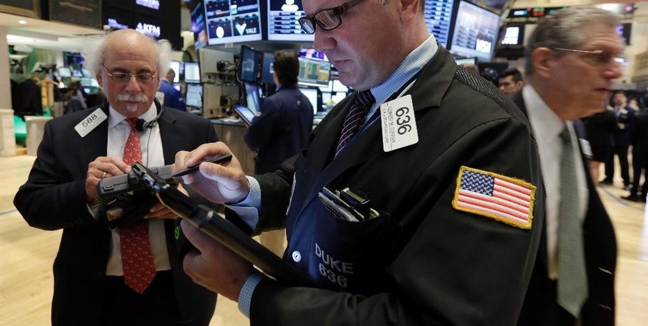 Traders Edward Curran, center, and Peter Tuchman, left, work on the floor of the New York Stock Exchange, Wednesday, Aug. 5, 2015. U.S. stocks are rising in early trading, shaking off a three-day slump, as the latest round of company earnings news brought several positive surprises. (AP Photo/Richard Drew)