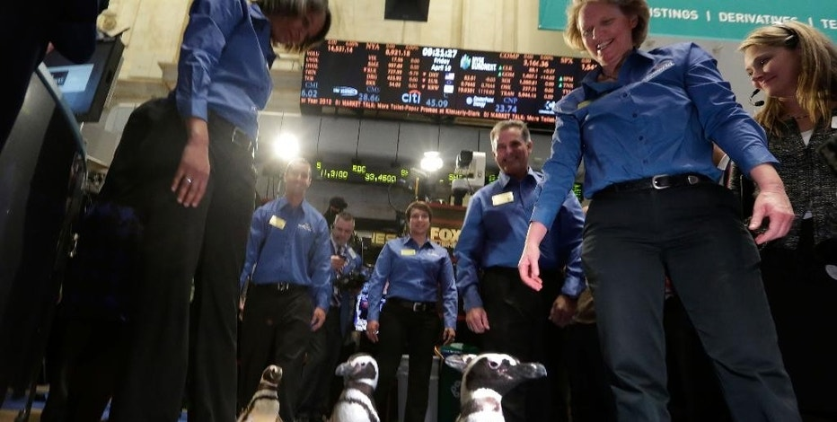 FILE - In this Friday, April 19, 2013, file photo, penguins from SeaWorld are escorted by their handlers on the floor of the New York Stock Exchange during the company's IPO, in New York. SeaWorld Entertainment Inc. (SEAS) on Thursday, Aug. 6, 2015, reported second-quarter profit of $5.8 million. (AP Photo/Richard Drew, File)