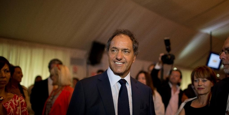 FILE - In this Dec. 10, 2014, file photo, Buenos Aires governor Daniel Scioli smiles at journalists and ambassadors invited to a cocktail at the Buenos Aires's province government residence in La Plata, Argentina. Voters are getting a chance on Sunday, August 9, 2015, to help decide who will replace President Crisitna Fernandez in the South American nation of 41 million as they cast ballots in open primaries for presidential candidates who have all but sealed the nominations in their respective parties. (AP Photo/Natacha Pisarenko)
