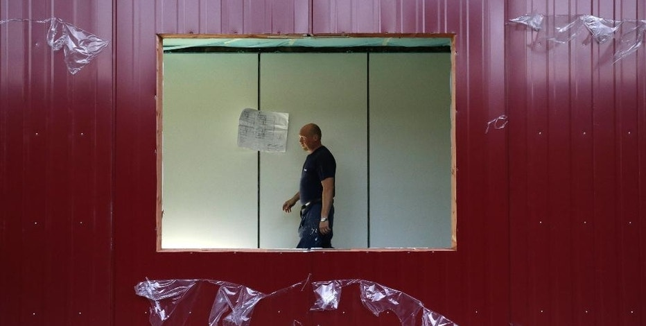A worker walks in a modular container at a plant in the village of Supikovice, Czech Republic, Tuesday, Aug. 11, 2015. The company which belongs to the modular division of the Paris-based Touax Group has been recently benefiting from orders from Germany that uses these modular like buildings to house thousands of migrants. (AP Photo/Petr David Josek)