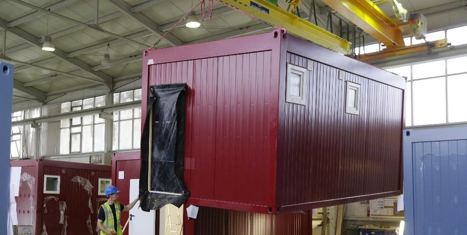 A worker moves a modular container at a plant in the village of Supikovice, Czech Republic, Tuesday, Aug. 11, 2015. The company which belongs to the modular division of the Paris-based Touax Group has been recently benefiting from orders from Germany that uses these modular like buildings to house thousands of migrants. (AP Photo/Petr David Josek)