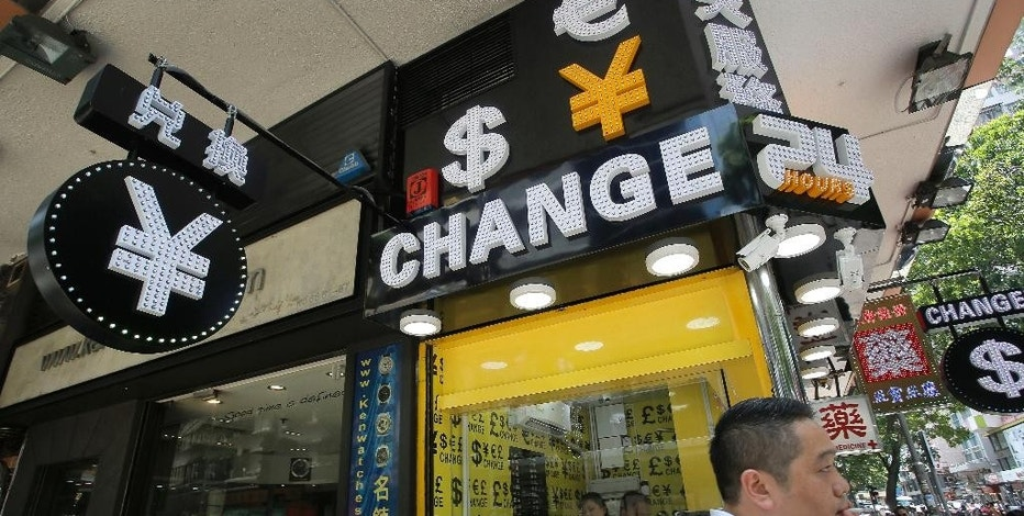 A man walks past a currency exchange shop in Hong Kong, Tuesday, Aug. 11, 2015. China devalued its tightly controlled currency Tuesday following a slump in trade, allowing the yuan's biggest one-day decline in a decade. (AP Photo/Vincent Yu)
