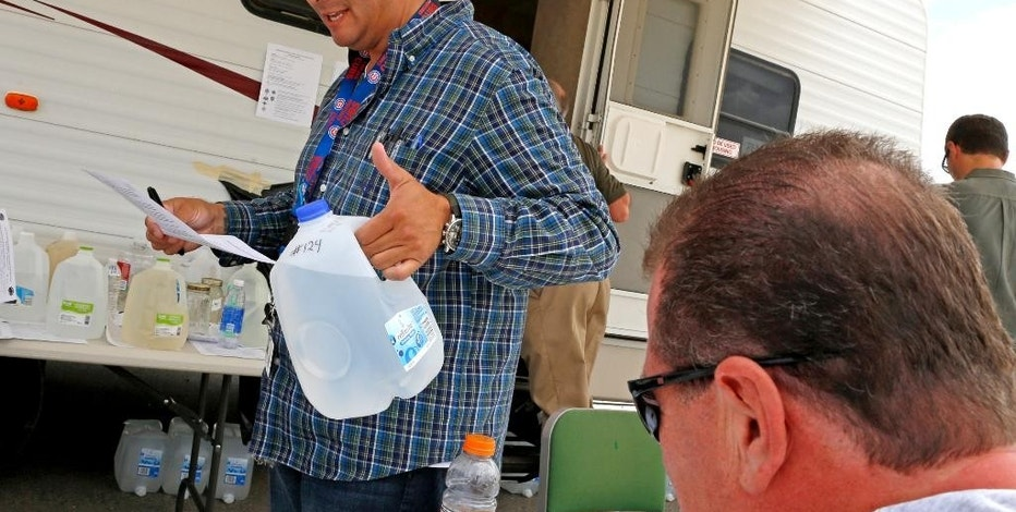 Alex Coca, a scientist with the New Mexico Environment Department, checks over paperwork before placing a jug of water on a table for testing at San Juan County's Lee Acres Sheriff's substation in Farmington, N.M., Monday, Aug. 10, 2015. A crew supervised by the U.S. Environmental Protection Agency has been blamed for causing a wastewater spill at an abandoned mine in Colorado that sent water laced with heavy metals, including lead and arsenic, downstream to the New Mexico municipalities of Aztec, Farmington and Kirtland over the weekend. (Alexa Rogals/The Daily Times via AP) MANDATORY CREDIT