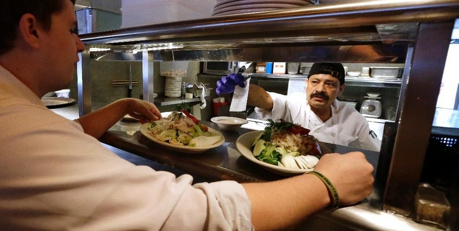 FILE - In this July 27, 2015 file photo, cook Bulmaro Sosa, right, goes over a food order with server Zachary DeYoung at an Ivar's restaurant in Seattle. The Labor Department releases second-quarter productivity data on Tuesday, Aug. 11, 2015. (AP Photo/Elaine Thompson, File)