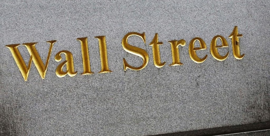 This July 6, 2015, photo shows a building with a Wall Street address in New York. Global stocks and Asian currencies fell Tuesday, Aug. 11, 2015, after China unexpectedly devalued the yuan in response to weakening trade and growth. (AP Photo/Mark Lennihan)