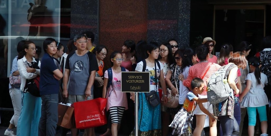 Chinese tourists queue to enter in a fashion store in Paris,  Wednesday, Aug. 12, 2015. China's currency fell further Wednesday following a surprise change in its exchange rate mechanism that rattled global markets and threatens to fan trade tensions with the United States and Europe. The central bank said the yuan's 1.9 percent devaluation Tuesday against the U.S. dollar, which was its biggest one-day fall in a decade, was due to changes aimed at making the tightly controlled currency more market-oriented. (AP Photo/Francois Mori)