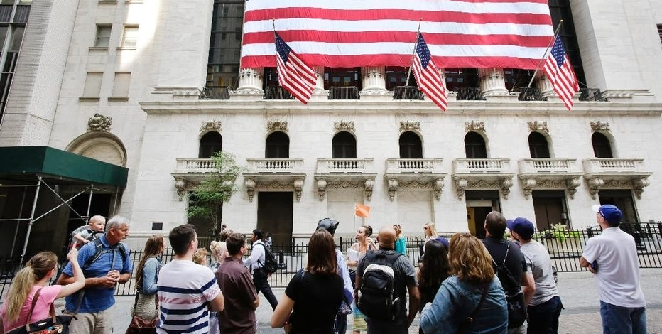 FILE - In this Monday, July 6, 2015, photo, tourists gather in front of the New York Stock Exchange. Shares sank Wednesday, Aug. 12, 2015, as China let its currency fall for a second day following a surprise devaluation that rattled global financial markets. (AP Photo/Mark Lennihan, File)