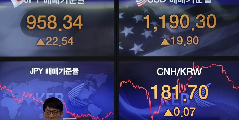 An employee is seated as screens showing foreign exchange rates are displayed at a bank in Seoul, South Korea, Thursday, Aug. 13, 2015. Asian stock markets stabilized Thursday after a two-day sell-off sparked by China's currency devaluation. China's yuan fell again but the decline was smaller than before. (AP Photo/Lee Jin-man)