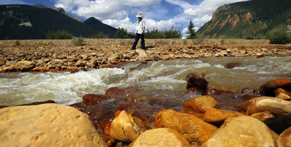 AP10ThingsToSee - Melanie Bergolc walks along the banks of Cement Creek in Silverton, Colo., Monday, Aug. 10, 2015. The area is a few miles downstream from the Gold King mine, where a wastewater accident several days earlier allowed water contaminated with heavy metals to pour into the creek that feeds rivers critical to survival on the largest Native American reservation in the United States and across the Southwest. (Jon Austria/The Daily Times via AP)