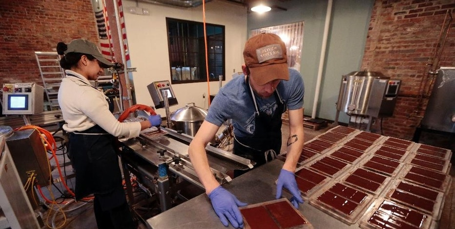 FILE - In this April 6, 2015, photo, Marta Crebilo, left, and Jason Thompson prepare chocolate molds at Olive and Sinclair Chocolate in the East Nashville area of Nashville, Tenn. The Labor Department releases the Producer Price Index for July on Friday, Aug. 14, 2015. (AP Photo/Mark Humphrey, File)