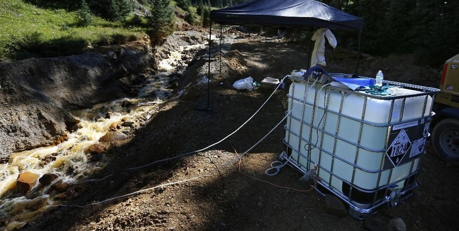 A plastic container feeds additives through tubes into mine wastewater flowing into a series of sediment retention ponds, part of danger mitigation in the aftermath of the blowout at the site of the Gold King Mine, outside Silverton, Colo., Friday, Aug. 14, 2015. Officials have said that federal contractors accidentally released more than 3 million gallons of wastewater laden with heavy metals last week at the Gold King Mine near Silverton. The pollution flowed downstream to New Mexico and Utah.  (AP Photo/Brennan Linsley)