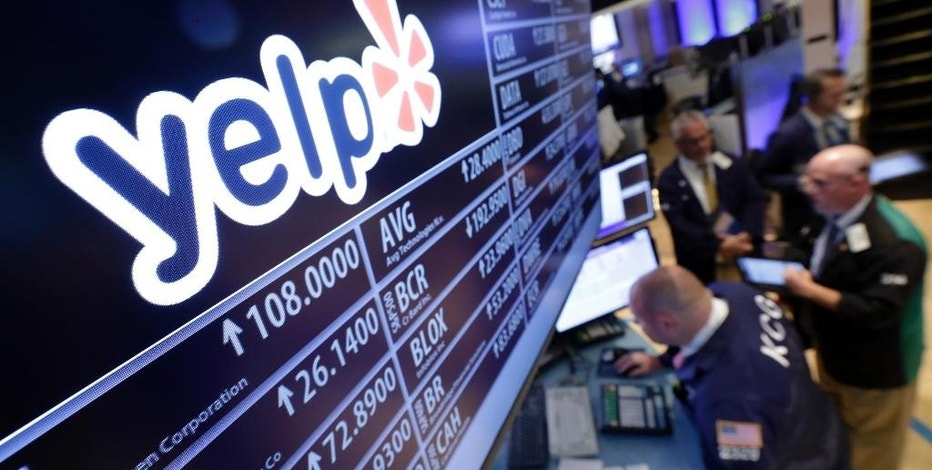 FILE - In this July 25, 2015 file photo, traders gather at the post that handles Yelp, on the floor of the New York Stock Exchange, Wednesday, July 29, 2015. While Google, Netflix and Amazon.com all soared to new heights after their recent quarterly reports, Apple, Twitter and Yelp were all ravaged for disappointing performances. (AP Photo/Richard Drew, File)