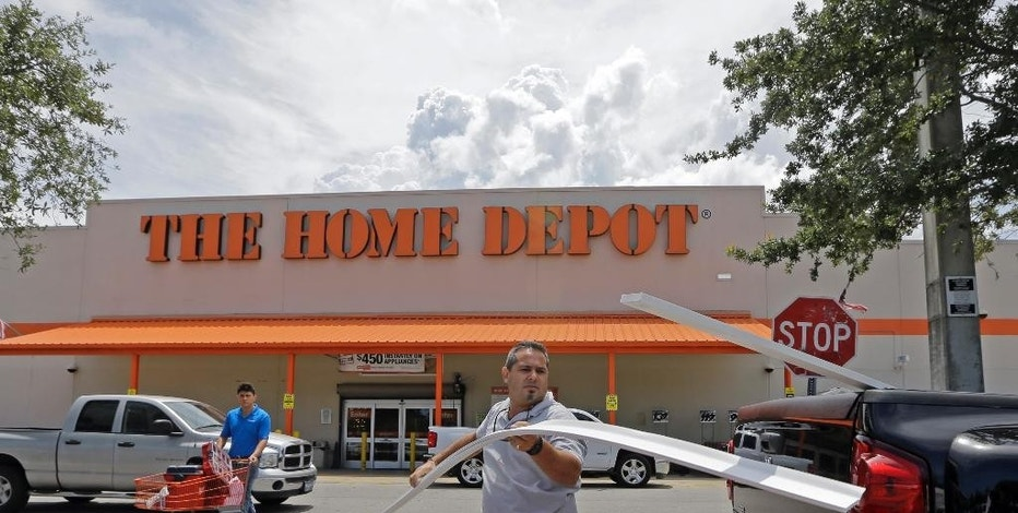 In this photo taken Monday, July 13, 2015, Vicente Aguiar loads garage door trims into his pickup truck outside a Home Depot in Hialeah, Fla. Home Depot reports quarterly financial results on Tuesday, Aug. 18, 2015.