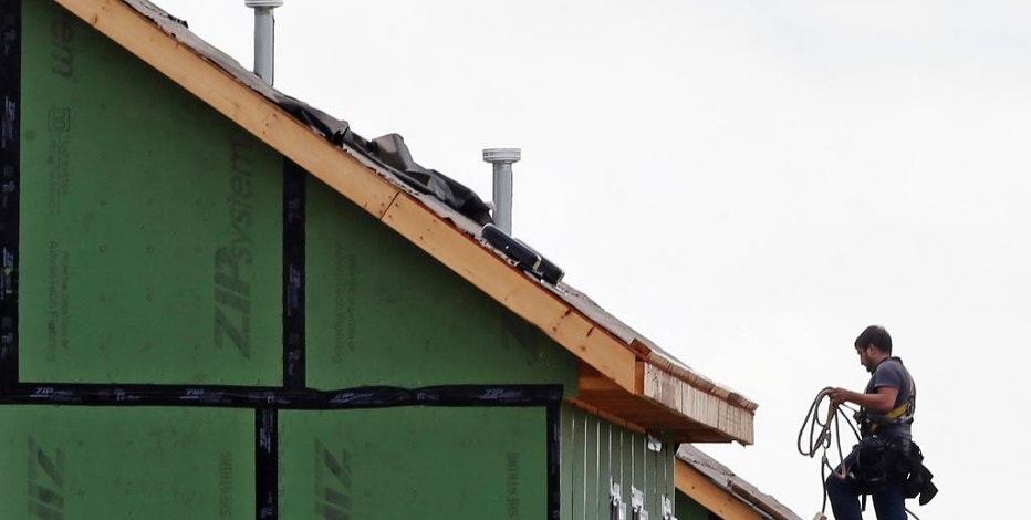 In this photo taken Tuesday, June 9, 2015, a roofer works on a home under construction in the Briar Chapel community in Chapel Hill, N.C. The Commerce Department releases housing starts for July on Tuesday, Aug. 18, 2015. (AP Photo/Gerry Broome)