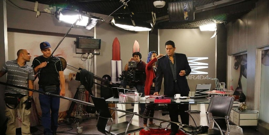 """In this Wednesday, May 27, 2015 photo, actor Carlos Cruz, right, gets ready for a scene from the Spanish-language soap opera """"Piel Salvaje,"""" or """"Wild Skin,"""" at the Radio Caracas Television RCTV studio in Caracas, Venezuela. """"Piel Salvaje"""" is the first independent production by what remained of RCTV after former President Hugo Chavez refused to renew its license and gave its seized transmission equipment to a state-funded network as punishment after accusing it of supporting a 2002 coup against him. (AP Photo/Ariana Cubillos)"""