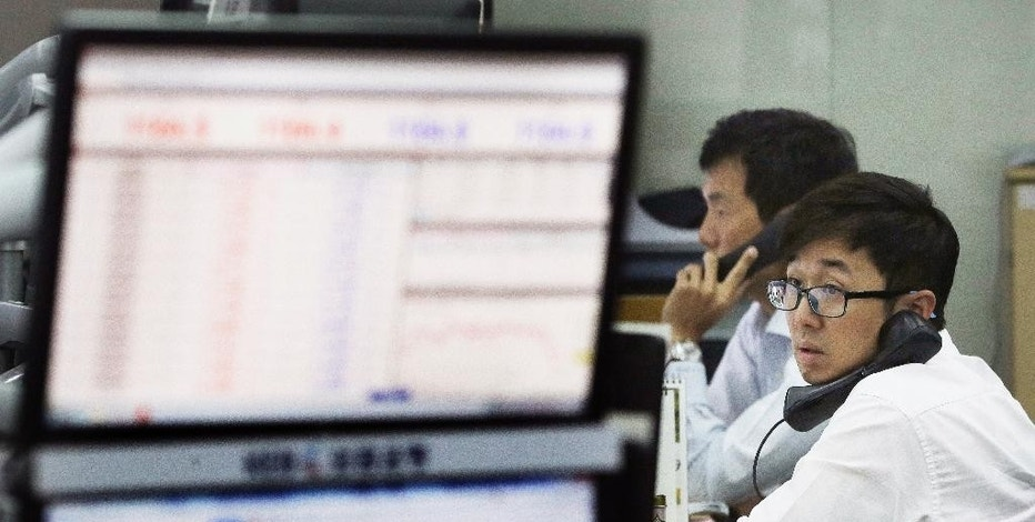Currency traders make a telephone call at the foreign exchange dealing room of the Korea Exchange Bank headquarters in Seoul, South Korea, Wednesday, Aug. 19, 2015. China's main Shanghai stock index slumped more than 4 percent on Wednesday, leading Asian stock markets lower a day after a sharp fall rattled investors around the world.(AP Photo/Ahn Young-joon)