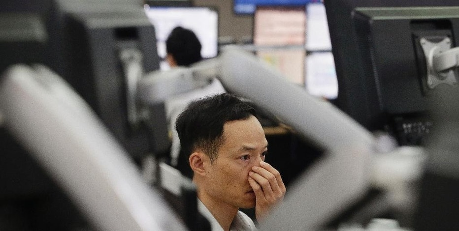 A currency trader watches a monitor screen at the foreign exchange dealing room of the Korea Exchange Bank headquarters in Seoul, South Korea, Wednesday, Aug. 19, 2015. China's main Shanghai stock index slumped more than 4 percent on Wednesday, leading Asian stock markets lower a day after a sharp fall rattled investors around the world.(AP Photo/Ahn Young-joon)