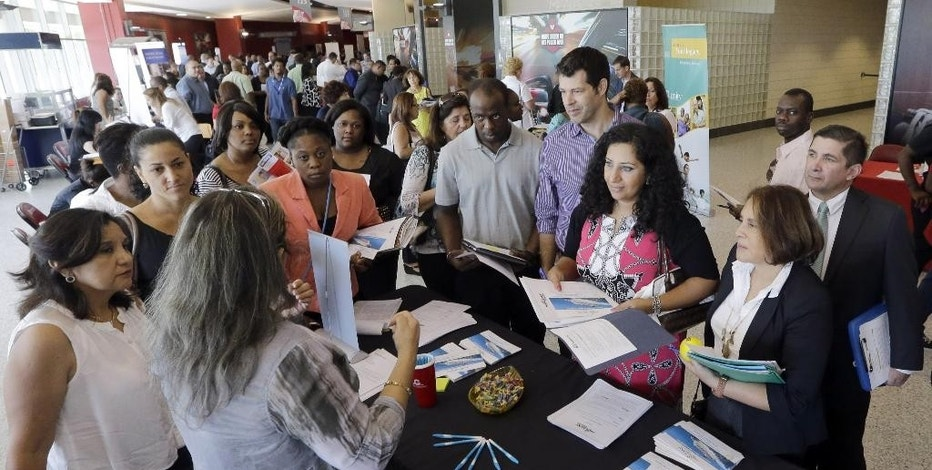 In this June 10, 2015, photo, job seekers get information at a job fair in Sunrise, Fla. The Labor Department releases weekly jobless claims on Thursday, Aug. 20, 2015.  (AP Photo/Alan Diaz)