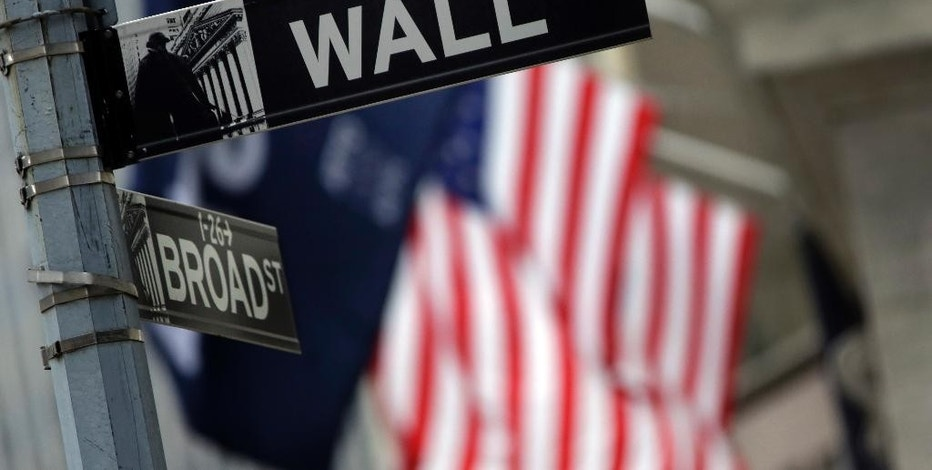 FILE - This Oct. 2, 2014 file photo shows a Wall Street sign adjacent to the New York Stock Exchange, in New York. A fresh sell-off of Chinese shares prompted renewed jitters across global markets on Thursday, Aug. 20, 2015. (AP Photo/Richard Drew, File)