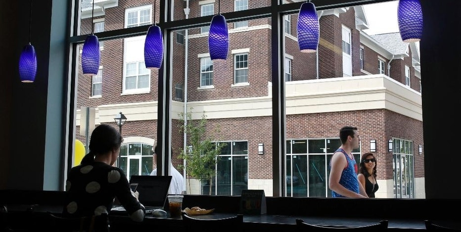 Newly constructed buildings are seen through the window of a new cafe in Campus Town at The College of New Jersey Wednesday, Aug. 19, 2015, in Ewing Township, N.J. At TCNJ, recognized as a top public liberal arts school, the first students are moving into the $120 million Campus Town development this month. The complex of buildings includes apartments for nearly 450 students, with more to come in a second phase of development, along with a book store. A yogurt shop, tavern and other businesses are to open soon. (AP Photo/Mel Evans)
