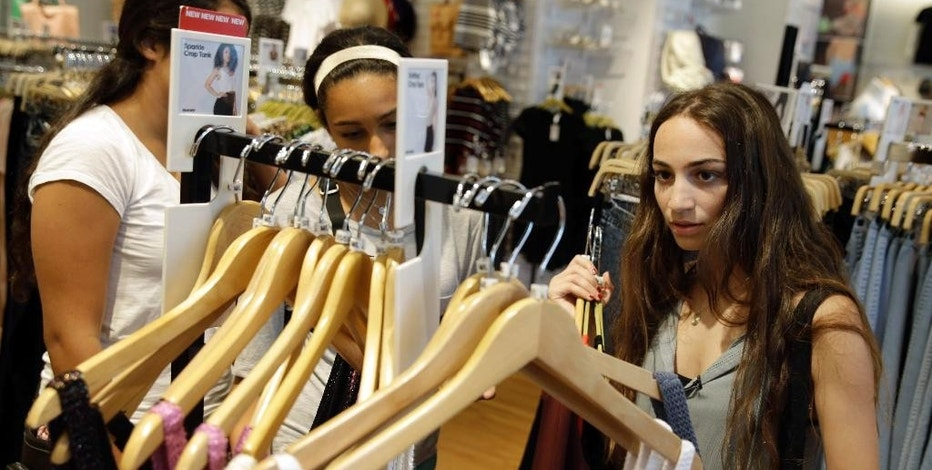 In this July 27, 2015, photo, Giulia Pugliese, 15, right, shops for clothes with friends at Roosevelt Field shopping mall in Garden City, N.Y. Teens are shopping like their parents during the back-to-school season, and that's putting a lot of pressure on retailers to change the way they market to them. More teens are thrifty nowadays, a habit picked up from their recession-scarred parents. (AP Photo/Seth Wenig)