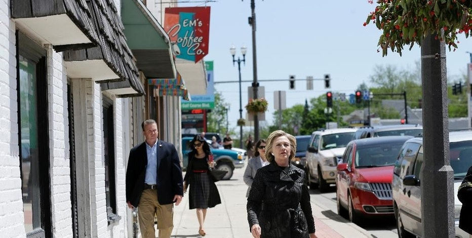 FILE - In this May 19, 2015 file photo, Democratic presidential candidate Hillary Rodham Clinton walks on Main Street while visiting local shops in Independence, Iowa. In her many visits to the leadoff caucus state, Clinton has included multiple remarks with regional references. The approach is a stylistic shift from Clinton's failed 2008 presidential bid, which began poorly with a third-place finish in the Iowa caucuses. (AP Photo/Charlie Neibergall, File)