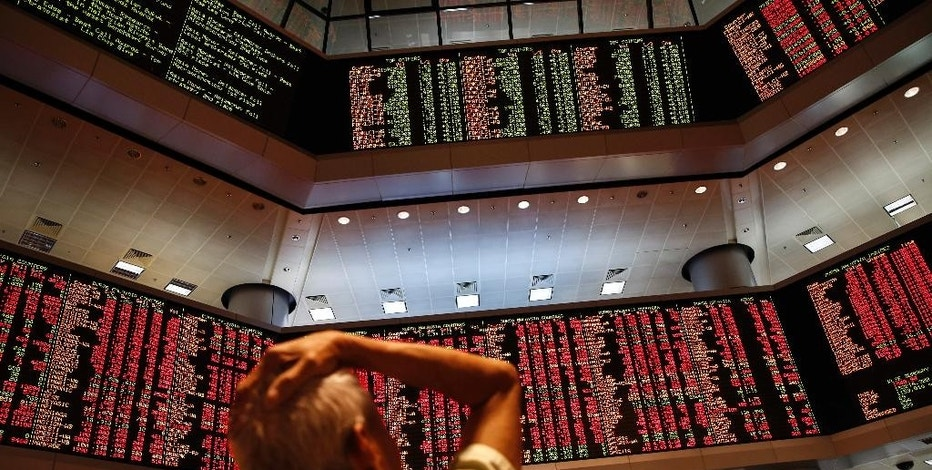 People watch trading boards at a private stock market gallery in Kuala Lumpur, Malaysia on Monday, Aug. 24, 2015. Stocks tumbled across Asia on Monday as investors shaken by the sell-off last week on Wall Street unloaded shares in practically every sector. (AP Photo/Joshua Paul)