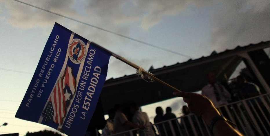 In this Aug. 20, 2015 photo, a supporter of the New Progressive Party waves a pro-statehood flag at a rally marking the party's 48th anniversary Manati, Puerto Rico. Advocates for making the Caribbean island the 51st state say the economic woes are strengthening their arguments. As a state, Puerto Rico's municipalities and public utilities would no longer be prohibited from restructuring their debts through bankruptcy. It would also receive more of certain kinds of federal funding that other states get. (AP Photo/Ricardo Arduengo)