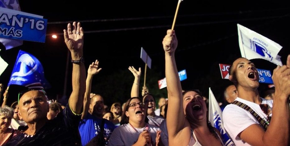 In this Aug. 20, 2015 photo, supporters of the New Progressive Party attend a rally marking the pro-statehood party's 48th anniversary Manati, Puerto Rico. Statehood supporters say joining the union would provide the kind of needed economic benefits Puerto Ricans get when they move to the mainland.  (AP Photo/Ricardo Arduengo)