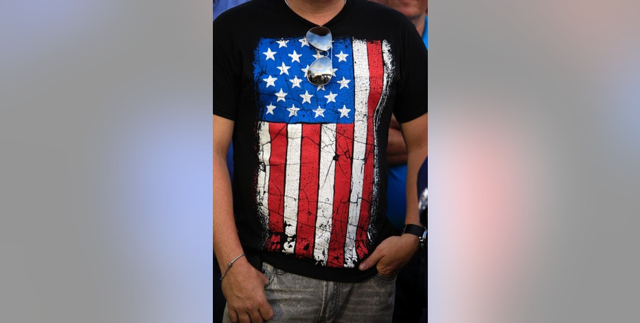 In this Aug. 20, 2015 photo, a New Progressive Party supporter wears a U.S. flag T-shirt during a rally marking the pro-statehood party's 48th anniversary in Manati, Puerto Rico. Statehood supporters say joining the union would, among other things, end their perceived second-class status. Even though residents are U.S. citizens, they cannot vote in the presidential election and have only one representative in Congress who has limited voting power. (AP Photo/Ricardo Arduengo)