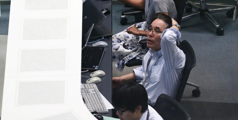 A worker of Tokyo Stock Exchange monitors stock prices on an electric screen during a trading session in Tokyo, Monday, Aug. 24, 2015. Stocks tumbled across Asia on Monday as investors shaken by the sell-off last week on Wall Street unloaded shares in practically every sector.  (AP Photo/Koji Sasahara)
