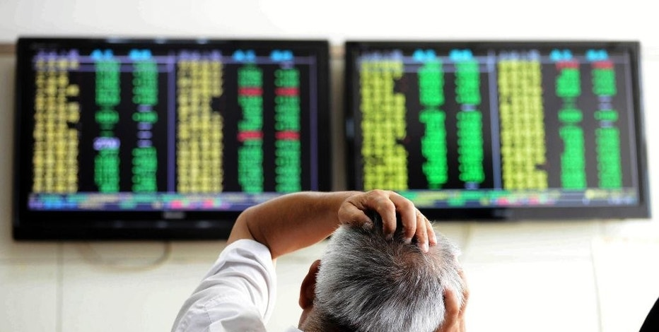 A Chinese stock investor reacts near a display for stock prices at a brokerage house in Qingdao in eastern China's Shandong province Tuesday, Aug. 25, 2015. Chinese stocks tumbled again Tuesday after their biggest decline in eight years while most other Asian markets rebounded from a day of heavy losses. (Chinatopix via AP) CHINA OUT