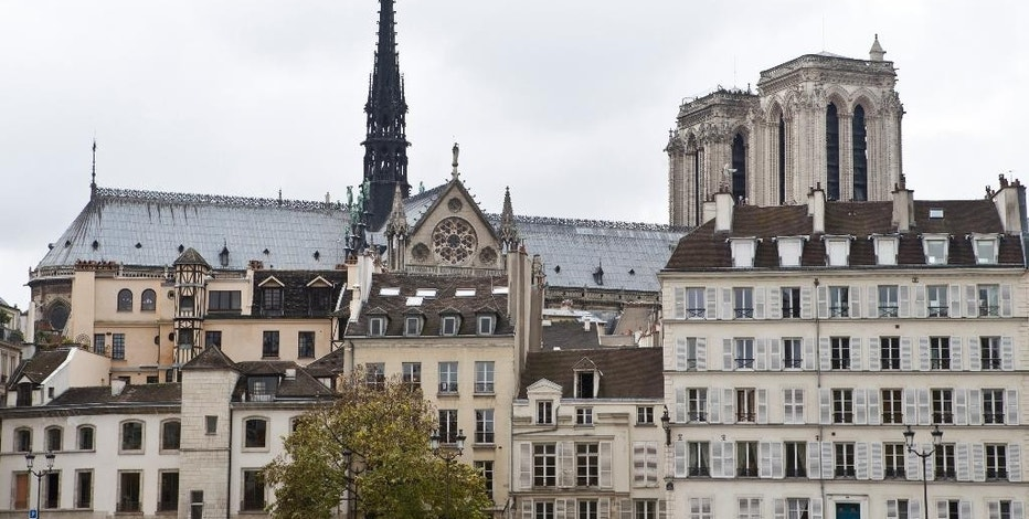 FILE - In this Nov.18, 2014 file photo, Notre Dame de Paris cathedral appears behind Paris buildings in Paris, France. Home-sharing company Airbnb has agreed to put a small tourist tax on rental apartments in Paris, following a request by Paris authorities. Paris, the most visited city in the world, is also the most popular city in the world for home sharing services. (AP Photo/Jacques Brinon, File)
