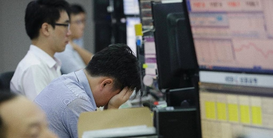 A currency trader covers his face with his hands at the foreign exchange dealing room of the Korea Exchange Bank headquarters in Seoul, South Korea, Wednesday, Aug. 26, 2015. Shares were mostly lower in Asia on Wednesday, after a move by China to cut its key interest rate failed to spark a sustained rally on Wall Street. Investors looked set for another white-knuckle day as Chinese, Hong Kong and Japan shares bobbled in and out of negative territory. (AP Photo/Ahn Young-joon)