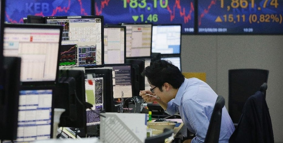 A currency trader eats lunch at the foreign exchange dealing room of the Korea Exchange Bank headquarters in Seoul, South Korea, Wednesday, Aug. 26, 2015. Shares were mostly lower in Asia on Wednesday, after a move by China to cut its key interest rate failed to spark a sustained rally on Wall Street. Investors looked set for another white-knuckle day as Chinese, Hong Kong and Japan shares bobbled in and out of negative territory. (AP Photo/Ahn Young-joon)