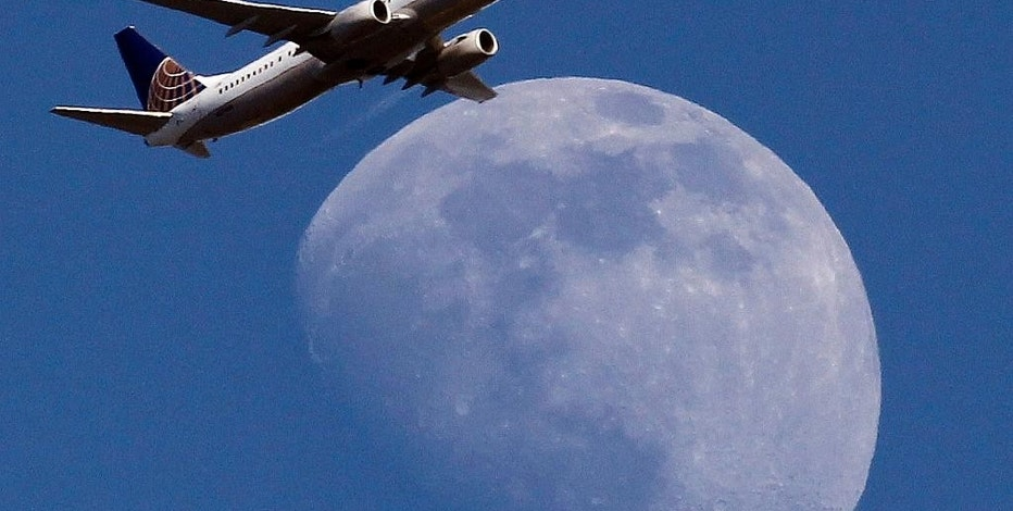 FILE - In this July 26, 2015, file photo, a United Airlines passenger airplane passes over Whittier, Calif., on its way to Los Angeles International Airport. Fliers in certain markets are seeing bargain flights as fare wars make a limited return. (AP Photo/Nick Ut, File)