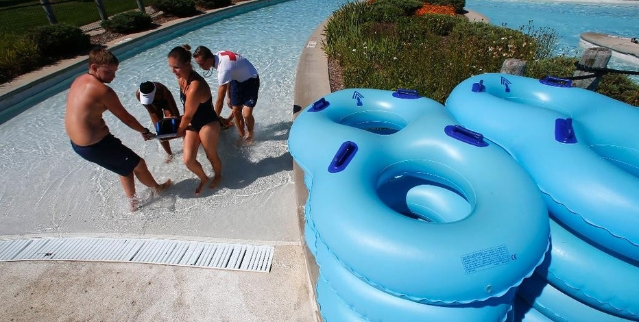 In this Aug. 5, 2015, photo, lifeguards simulate a shallow water rescue on a backboard from a lazy river at the Rolling Hills Water Park in Ypsilanti, Mich. Concern is growing about risks present even when most waterpark water is shallower than 3 feet. (AP Photo/Paul Sancya)