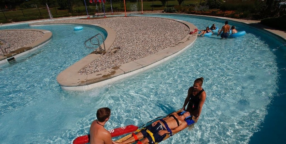 In this Aug. 5, 2015, photo, lifeguards Sam Hargrove, from left, David Frey and Becca Weil simulate a shallow water rescue in a lazy river at the Rolling Hills Water Park in Ypsilanti, Mich. Concern is growing about risks present even when most waterpark water is shallower than 3 feet. (AP Photo/Paul Sancya)