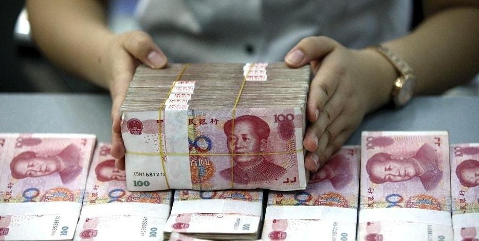 A bank clerk counts renminbi banknotes in a bank branch in Huaibei in central China's Anhui province Wednesday Aug. 26, 2015.   Asian stocks rose Wednesday after a rocky start following Beijing's decision to cut a key interest rate to help stabilize gyrating financial markets and free up more funding to counter short liquidity. (Chinatopix Via AP) CHINA OUT
