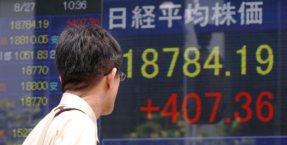 A man looks at an electronic stock indicator of a securities firm in Tokyo, Thursday, Aug. 27, 2015. Asian stocks rose Thursday after Wall Street soared overnight, breaking a six-day string of losses. (AP Photo/Shizuo Kambayashi)