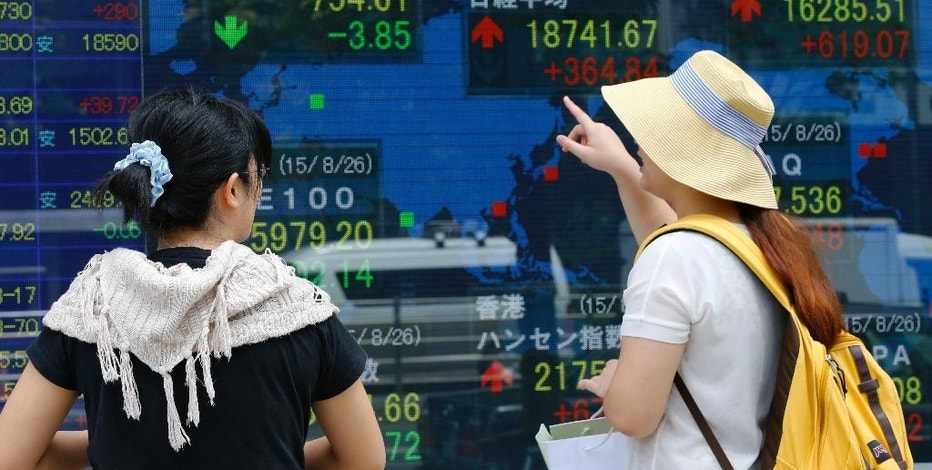 Women look at an electronic stock indicator of a securities firm in Tokyo, Thursday, Aug. 27, 2015. Asian stocks rose Thursday after Wall Street soared overnight, breaking a six-day string of losses. (AP Photo/Shizuo Kambayashi)