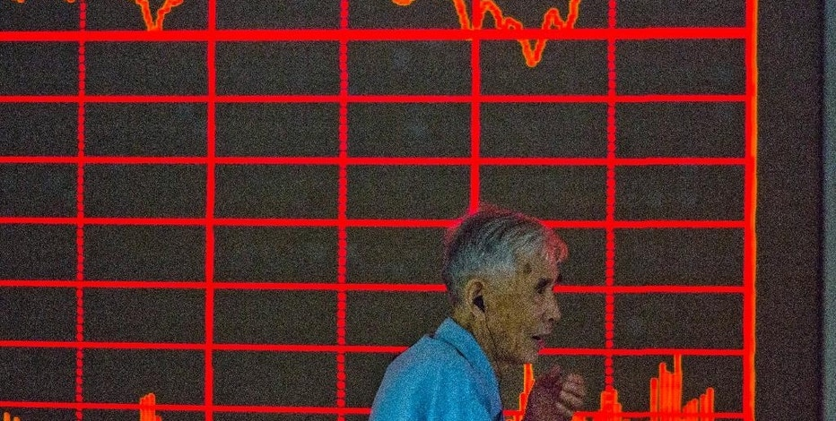 A Chinese investor walks past a display of the Shanghai Composite Index at a brokerage in Beijing on Thursday, Aug. 27, 2015. China's key stock market index surged 5.3 percent Thursday, its biggest gain in eight weeks, as markets across Asia rose following Wall Street's rebound, giving investors some relief after gut-wrenching global losses. (AP Photo/Ng Han Guan)