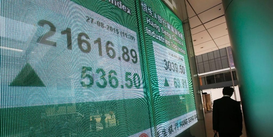 A man walks past a bank's electronic board showing the Hong Kong share index outside a local bank in Hong Kong Thursday, Aug. 27, 2015. China's main stock market index has surged 5.3 percent, its biggest gain in eight weeks, as Asian markets rose following Wall Street's overnight rebound. (AP Photo/Vincent Yu)