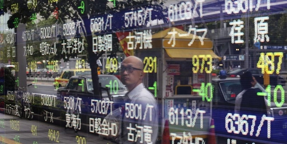 A man is reflected on the electronic board of a securities firm in Tokyo, Monday, Aug. 31, 2015. Asian stocks fell Monday after a U.S. Federal Reserve official suggested a September interest rate hike still was possible and Japanese factory activity weakened (AP Photo/Koji Sasahara)